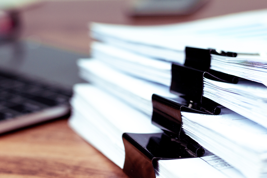 A picture of a stack of papers ready to be processed into a digital document management system.